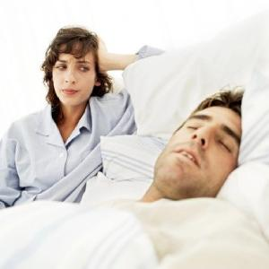 worried woman looking at a sleeping man